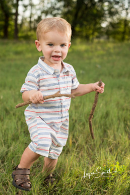 Boy in field with sticks